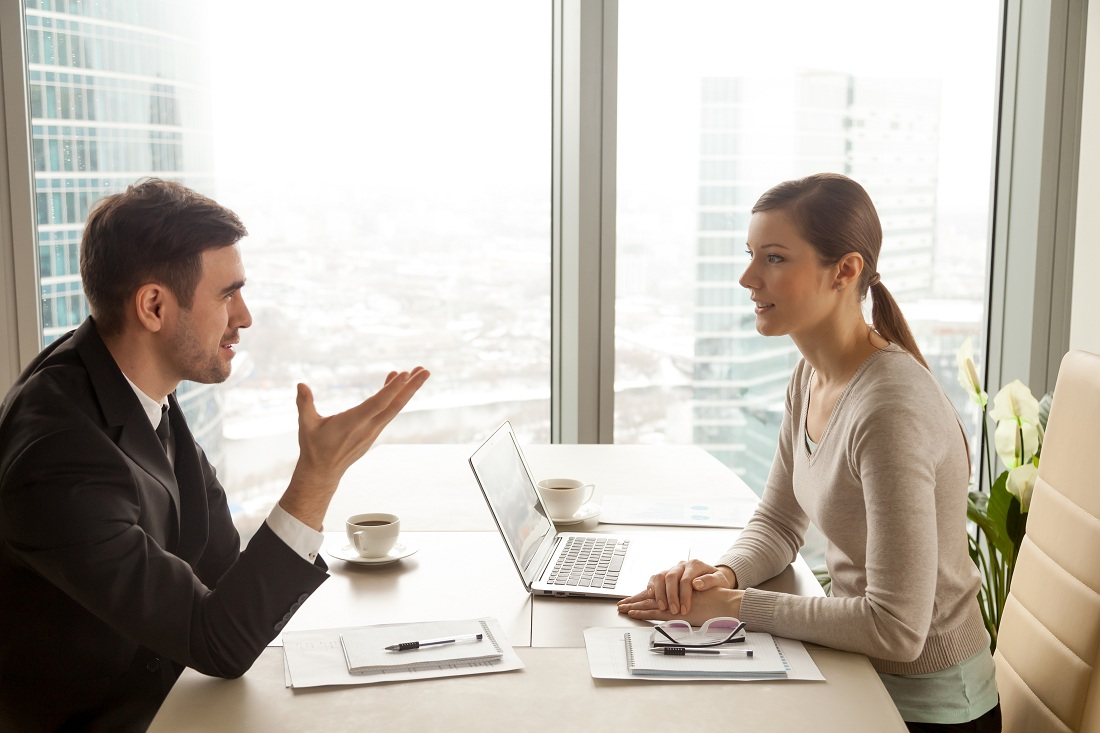 businessman and businesswoman discussing work at office desk
